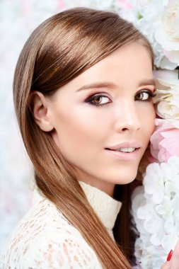 Close-up portrait of a beautiful young woman over floral background. Spring mood. Natural cosmetics, make-up, skincare.