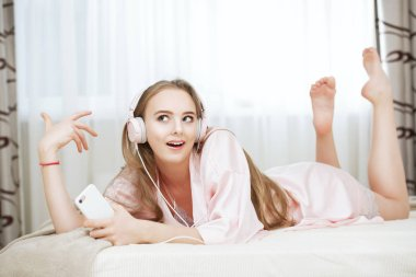 Portrait of an attractive young girl lying in a pajamas with headphones on the floor near the bed at home. Beauty, cosmetics.