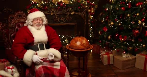 Santa Claus sedí v kožené židli pokryté přikrývkou a chytá dárkové krabice v místnosti zařízené na Vánoce. Vánoce a nový rok čas , dodání dárků z ruky do ruky