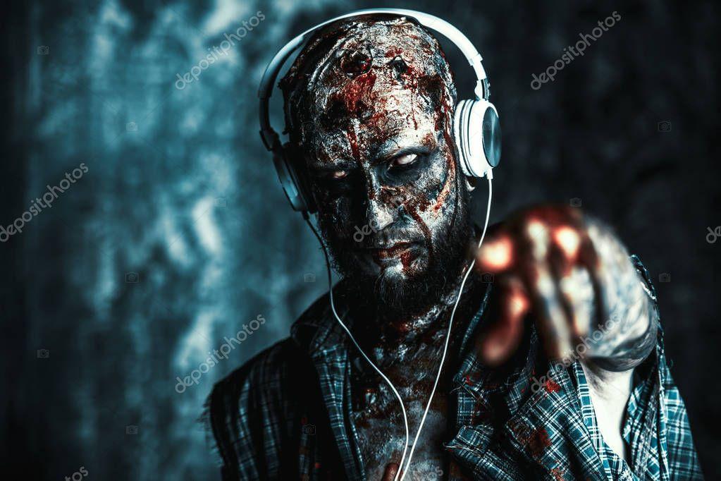 Creepy scary zombie is listening to music with headphones. Halloween. Horror film. stock vector