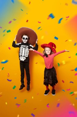 Halloween. Two happy kids in witch and skeleton costumes are jumping over yellow background. Dia de los muertos. Day of The Dead. Copy space. stock vector
