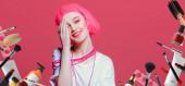 Porträt eines fröhlichen Mädchens mit leuchtend rosa Haaren und rosa Make-up, das von Make-up, Haar- und Nagelkosmetik träumt. Rosa Hintergrund. Schönheit, Modekonzept. Jugendstil.