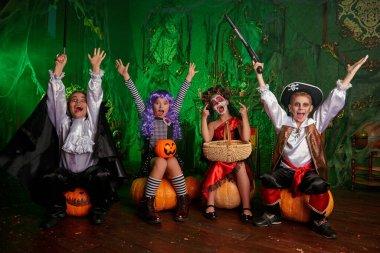 Cadılar Bayramı. Karnaval kostümlü komik çocuklar Cadılar Bayramı 'nda eski şatoda balkabaklarıyla oturuyorlar..