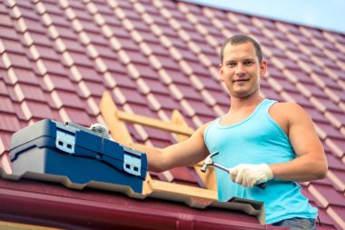 portrait of a man with a toolbox on the roof of the house during repair on the background of roof tiles