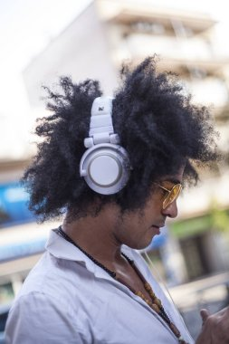 attractive and latino man with afro hair and yellow pilot glasses on a street and listen music with headphones and smart phone