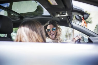 Young and beautiful women singing and dancing to the rhythm of music in their car