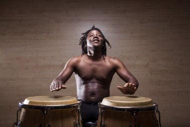 young african rastafarian man enjoys rehearsing and plays congas