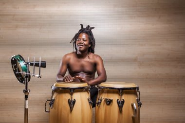 young african rastafarian man enjoys rehearsing and plays the conga, tambourine and cowbell