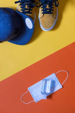 Vertical mockup, mustard colored shoes on two colors yellow and orange background and a blue cap, hydroalcoholic gel and face mask, copy space