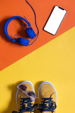 vertical mockup, mustard colored shoes on two colors yellow and orange background , smart phone with white screen and headphones, copy space