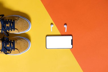 vertical mockup, mustard colored shoes on two colors yellow and orange background , smart phone with white screen and earphones, copy space