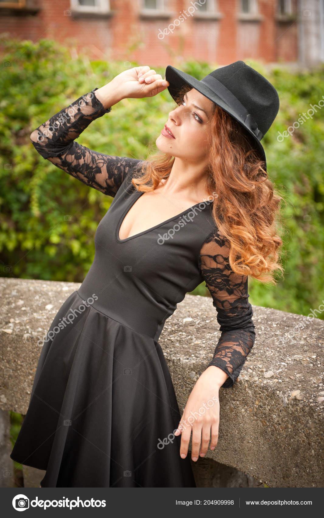 5498c725165eab Charmante junge leicht Braunes Haar Brünette Frau mit großen schwarzen Hut  und Bluse mit Spitzen Ärmel. Sexy wunderschöne junge Frau mit lockiges Haar  ...