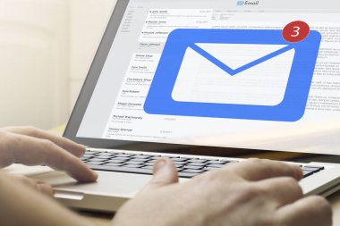 Hands using laptop on desktop with mail