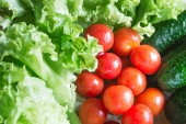 The concept of healthy eating. Background with vegetables. Green salad and tomatoes
