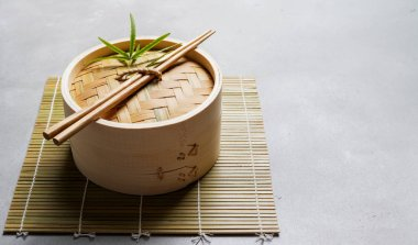 Traditional chinese bamboo steamer for steamed dumplings Dim Sums with chopsticks on light surface with copy space. Asian food background.