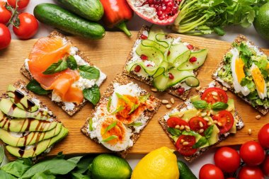 Top view of Superfood protein toast with delicious toppings on top: smoked salmon, spinach, cucumber, tomato and cream cheese on wooden long cutting board among vegetables ingredients. healthy snacks.