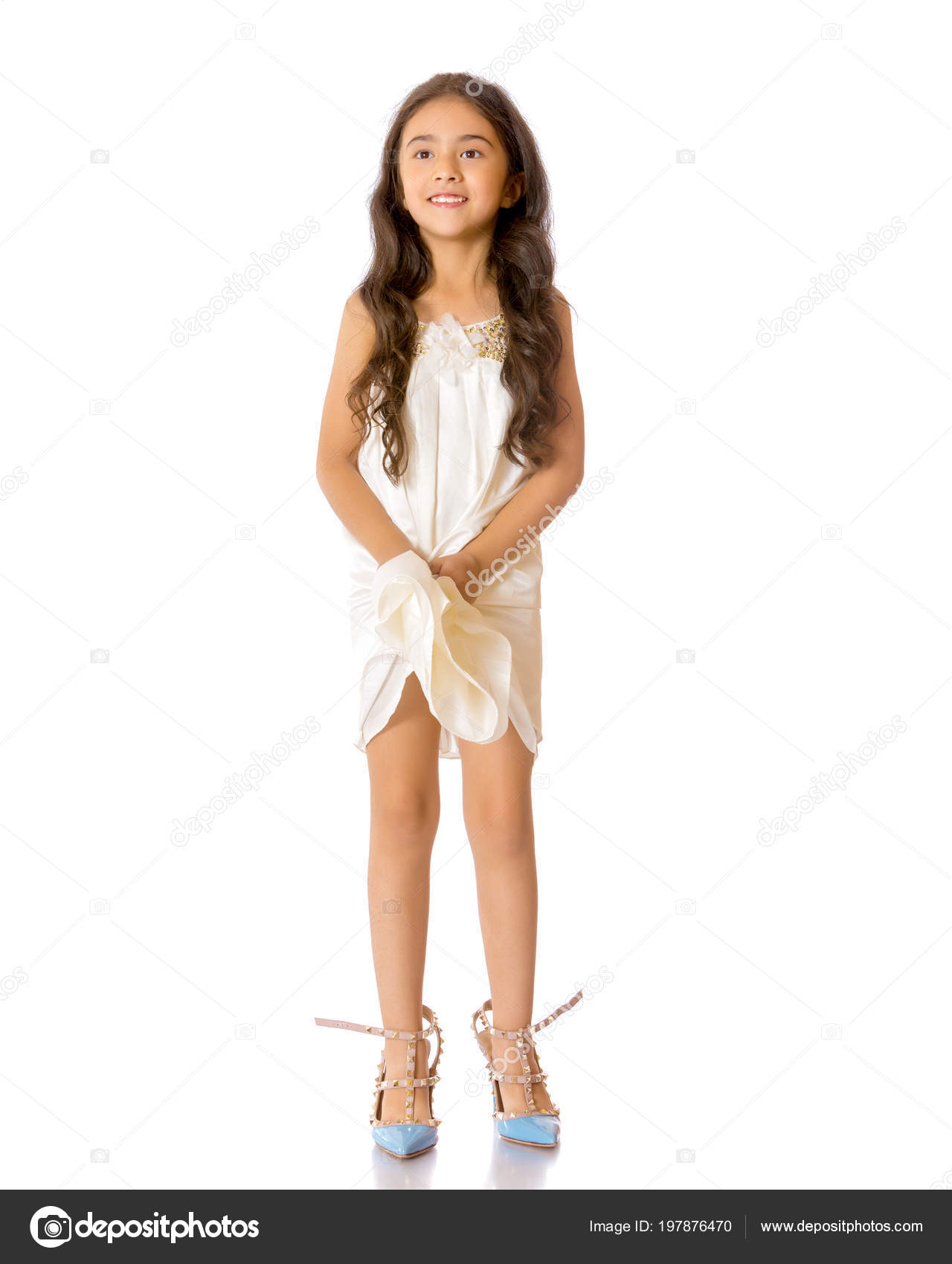 A small Asian girl in high-heeled shoes.– stock image