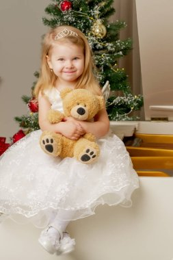A little girl is sitting on a white piano with a teddy bear.