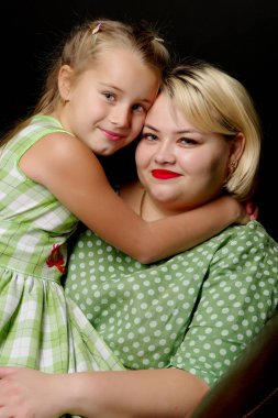 Mom and daughter are hugging on a black background.