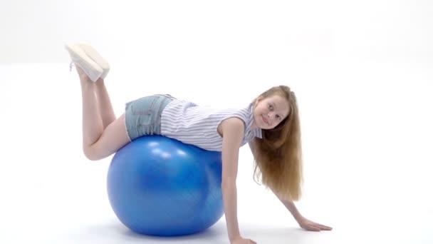 kleines Mädchen macht Übungen auf einem großen Ball für Fitness.