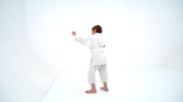 Egy kisfiú fehér kimonó teljesíti fúj