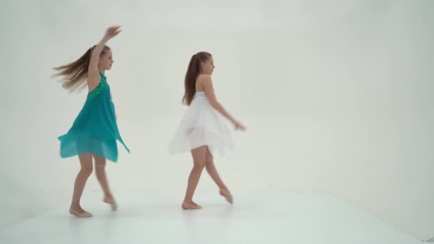 Twin Sisters Wearing Sport Dresses Dancing Against White Background.