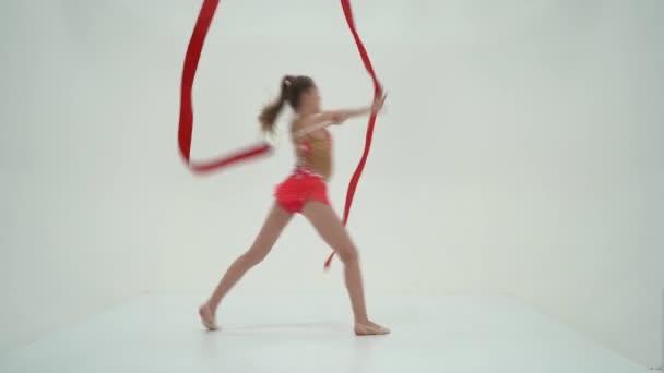 Lány torna elvégzi gyakorlatokat szalaggal.