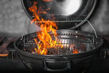 New modern barbecue grill with coals on black background