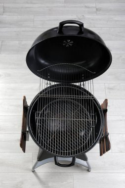 New modern barbecue grill on wooden floor