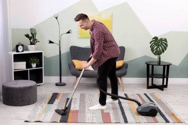 Young man removing dirt from carpet with vacuum cleaner at home