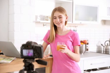 Cute teenage blogger with glass of juice recording video at table