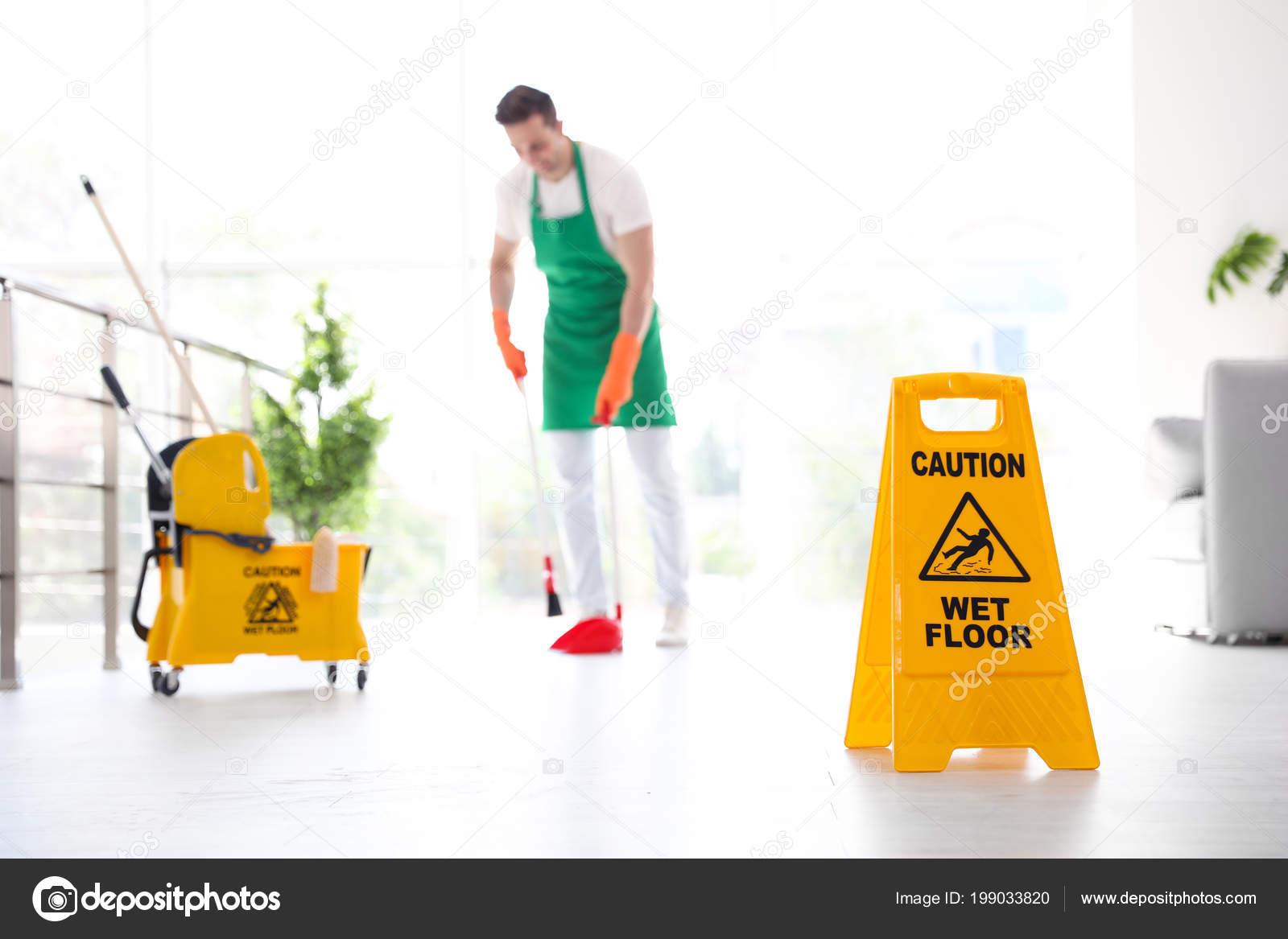 Segno sicurezza con frase attenzione pavimento bagnato giovane