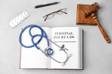 Flat lay composition with book, gavel, pills and stethoscope on grey background. Personal injury law concept