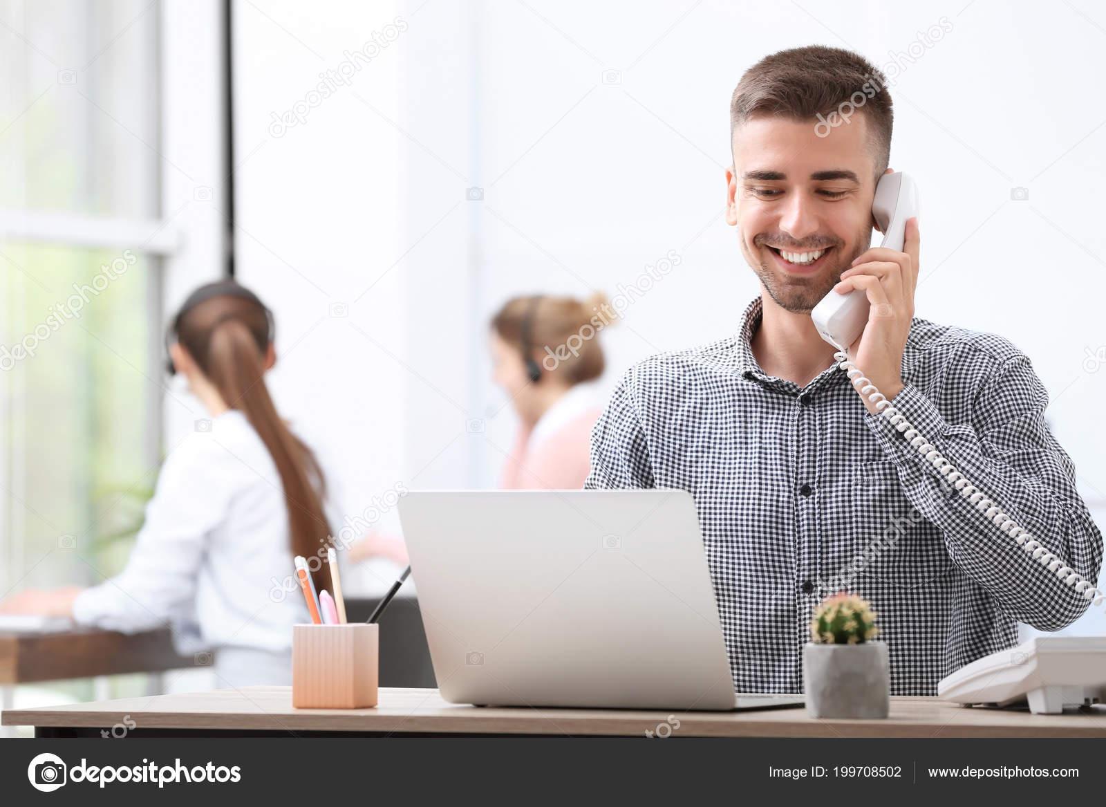 Mâle réceptionniste parlant téléphone comptoir bureau u2014 photographie
