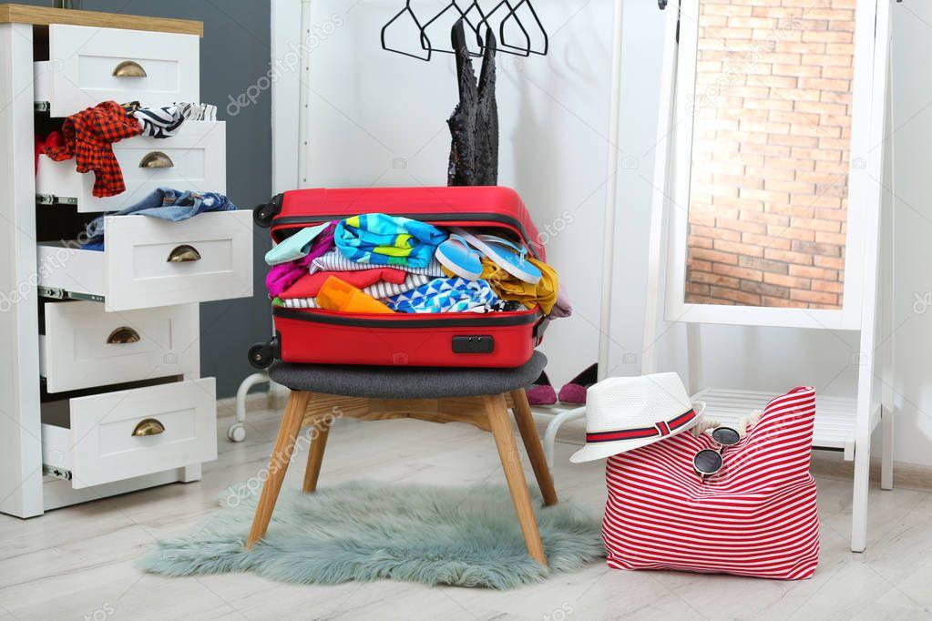 Valigia con spiaggia vestiti accessori sgabello spogliatoio u foto