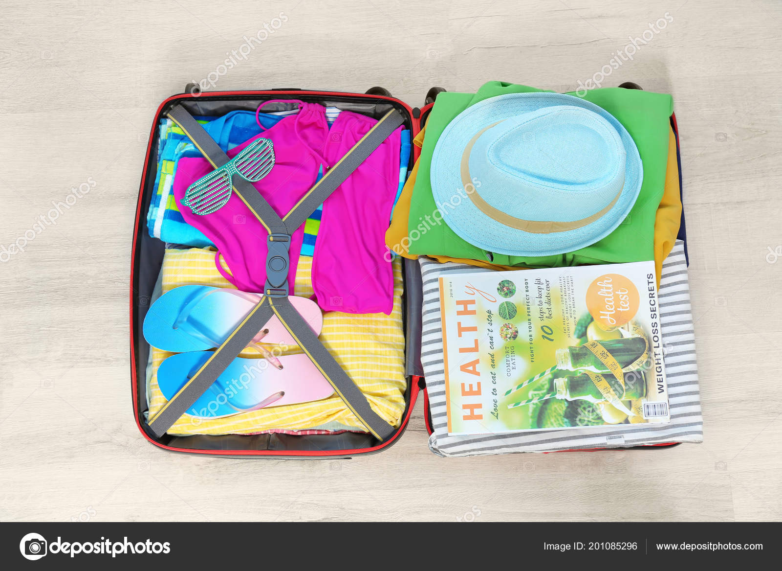 open suitcase different clothes accessories floor top view packing