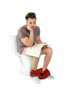 Young man with newspaper sitting on toilet bowl. Isolated on white