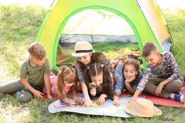 Little children with map near tent outdoors. Summer camp