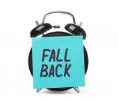 Sveglia e nota di Sticky Notes con parole Fall Back su priorità bassa bianca. Concetto di tempo