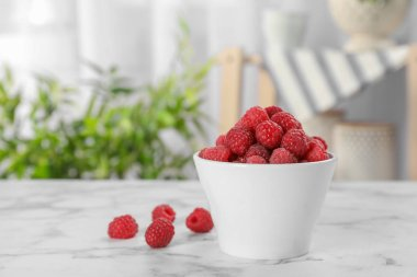 Bowl with ripe aromatic raspberries on table