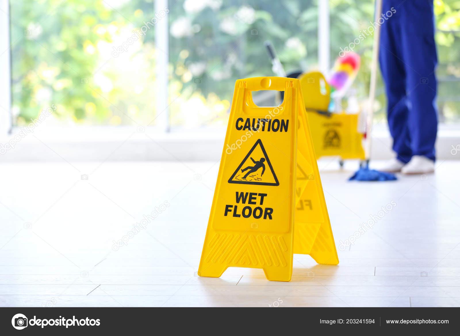 Segno sicurezza con frase attenzione pavimento bagnato detergente