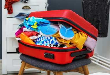 Suitcase with beach clothes and accessories on stool indoors
