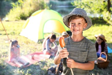 Little boy with fried sausage outdoors. Summer camp