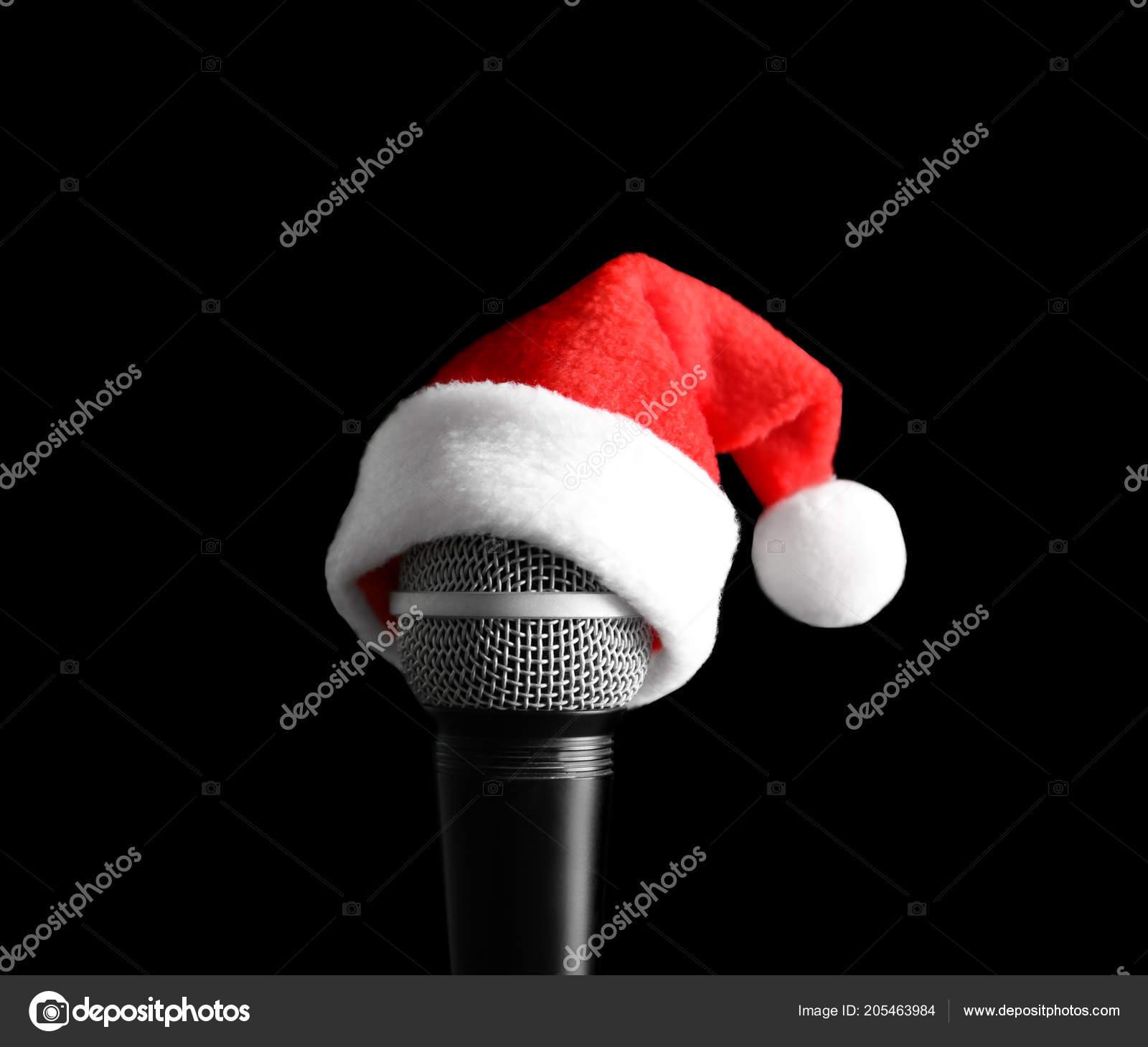 314867c0381c9 Microphone with Santa hat on black background. Christmas music concept —  Photo by liudmilachernetska gmail.com