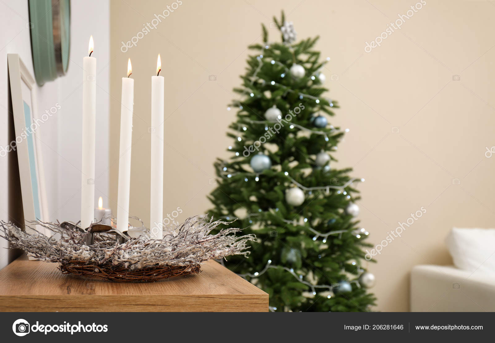 burning candles with wreath on table and christmas tree in stylish living room interior photo by liudmilachernetskagmailcom