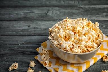 Bowl of tasty popcorn on wooden background