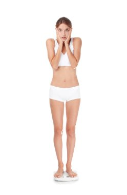 Worried young woman using bathroom scales on white background. Weight loss diet