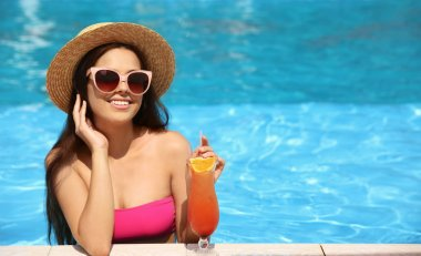 Beautiful young woman with cocktail in blue swimming pool