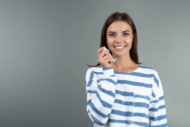 Young woman with asthma inhaler and space for text on color background