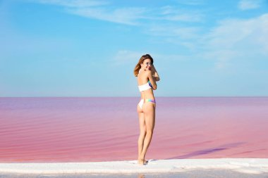 Beautiful woman in swimsuit standing near pink lake on sunny day